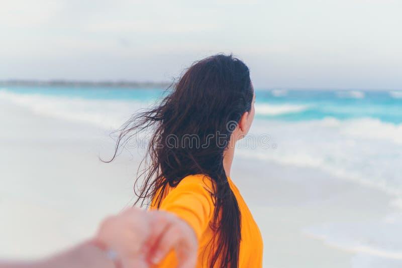 Novio despu?s de la novia que lleva a cabo las manos en la playa salvaje blanca que r?e y que sonr?e fotos de archivo libres de regalías