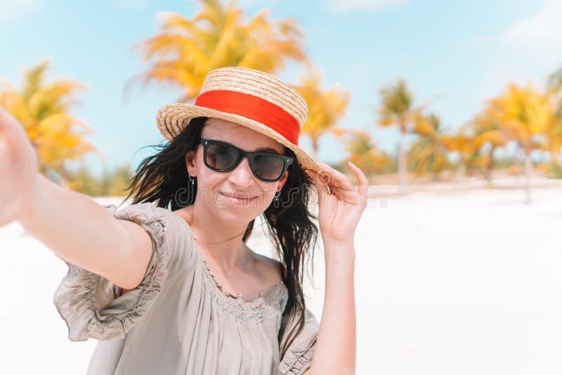 Novio despu?s de la novia que lleva a cabo las manos en la playa salvaje blanca que r?e y que sonr?e imagen de archivo