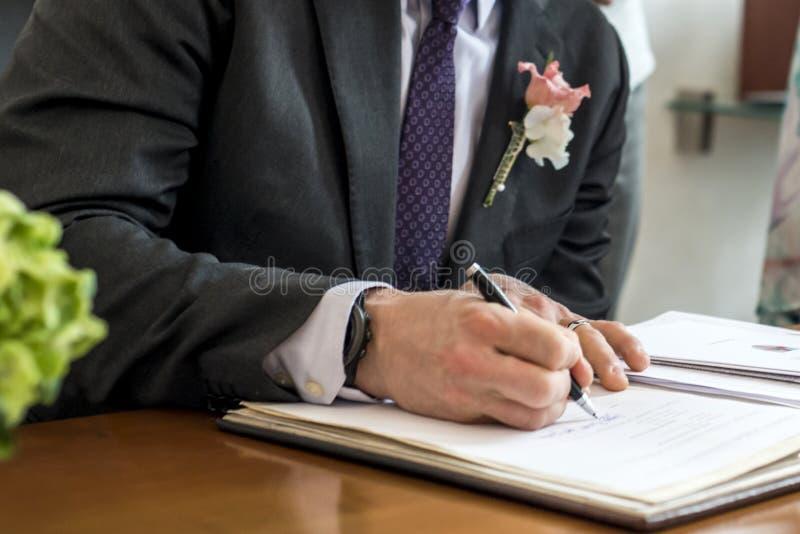 Novio elegante de la boda que firma la pluma de tenencia alemana del registro de la boda y pares del documento oficial foto de archivo