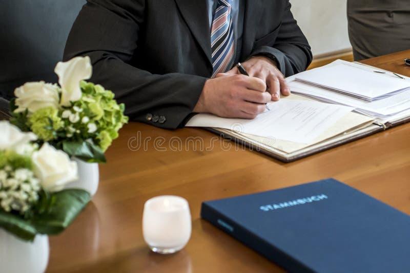 Novio elegante de la boda que firma la pluma de tenencia alemana del registro de la boda y pares del documento oficial imagenes de archivo