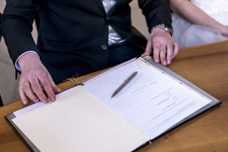Novio elegante de la boda que firma la pluma de tenencia alemana del registro de la boda y pares del documento oficial foto de archivo libre de regalías