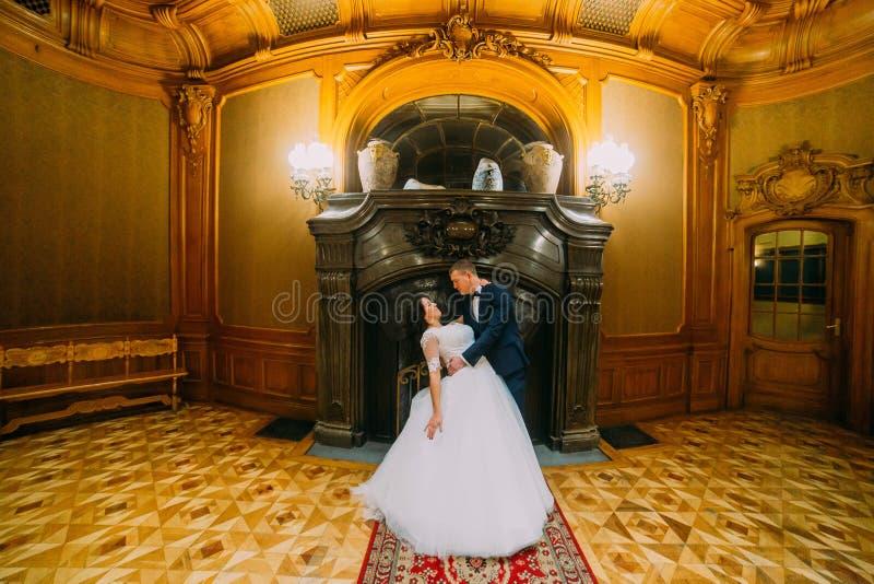 Novio elegante elegante que sumerge a su esposa encantadora, presentando en interior rico de la mansión clásica vieja imagenes de archivo