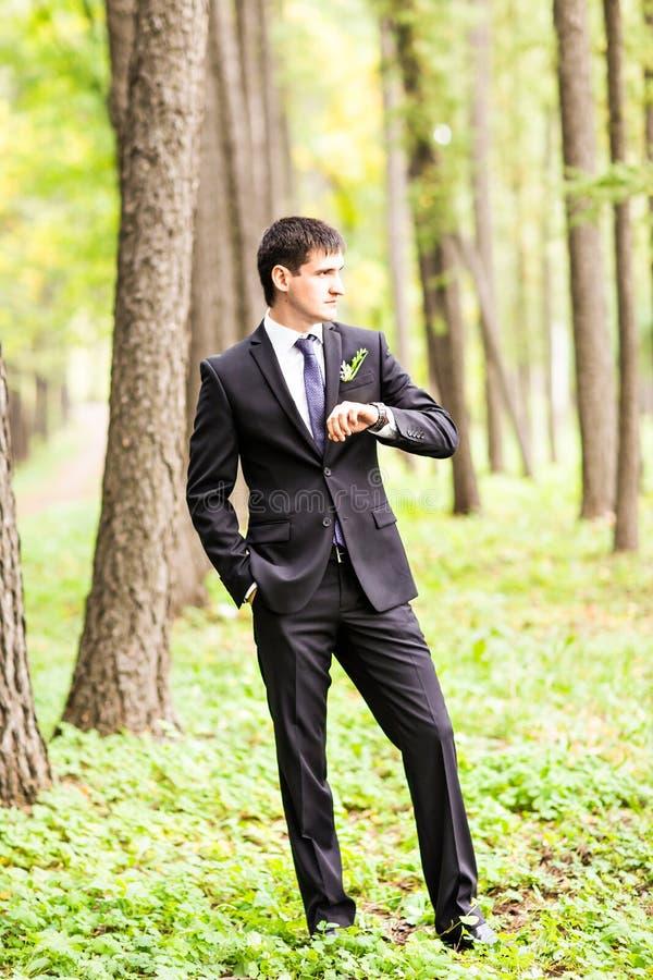 Novio elegante feliz magnífico que mira en su reloj al aire libre fotos de archivo