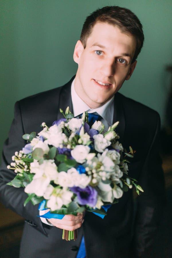 Novio elegante hermoso en traje negro con un primer del ramo de la boda imagen de archivo