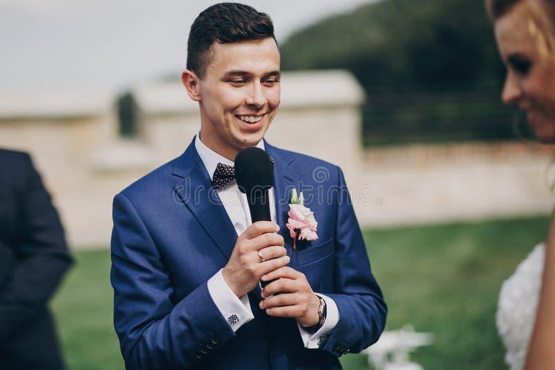 Novio elegante que pronuncia voto a su novia hermosa durante matrimonio Novio que pronuncia discurso y que sostiene el micrófono  imagen de archivo libre de regalías