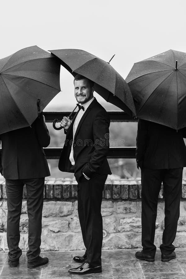 Novio elegante y padrinos de boda que se colocan debajo del paraguas negro y del po fotografía de archivo libre de regalías