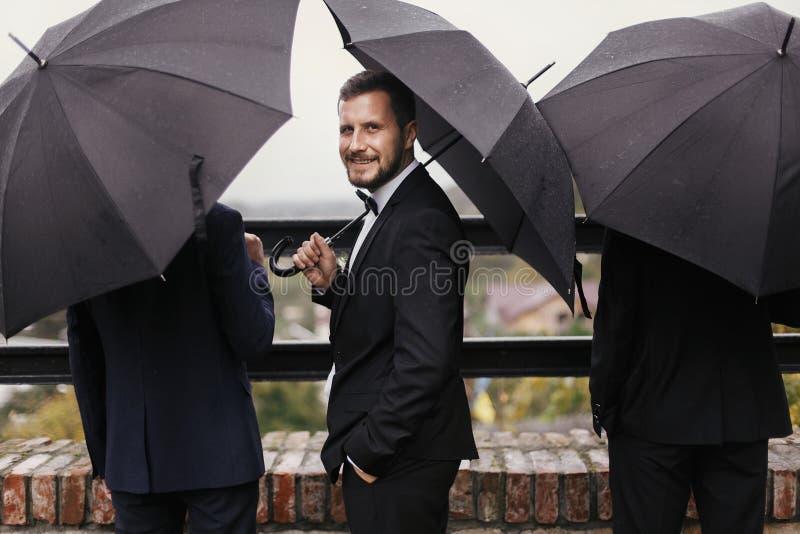 Novio elegante y padrinos de boda que se colocan debajo del paraguas negro y del po fotografía de archivo