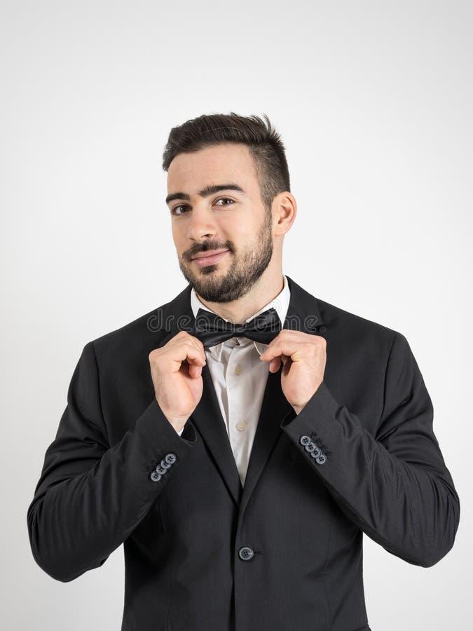 Novio emocionado divertido que ajusta su corbata de lazo que mira la cámara fotografía de archivo libre de regalías