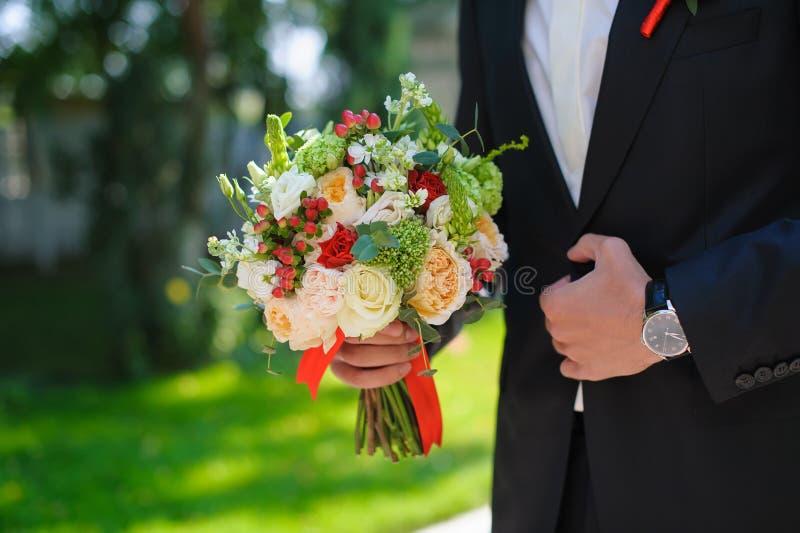 Novio en el traje que sostiene el ramo hermoso de las flores imágenes de archivo libres de regalías