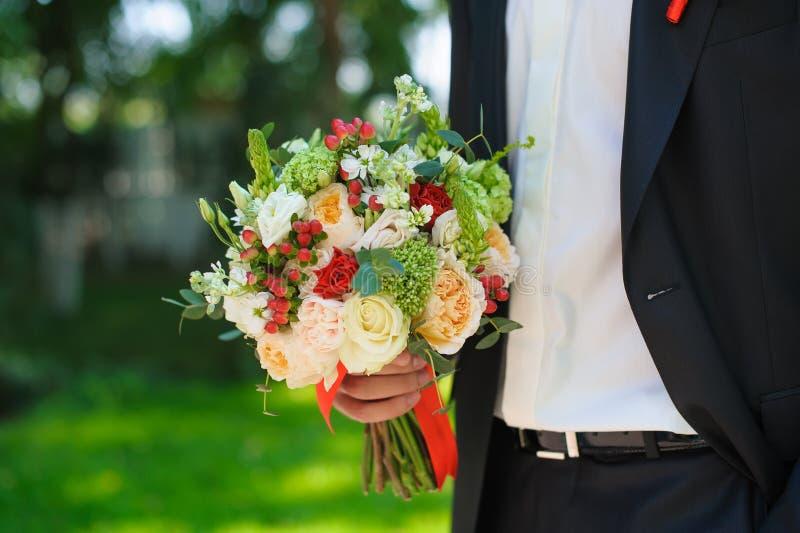 Novio en el traje que sostiene el ramo hermoso de las flores fotos de archivo