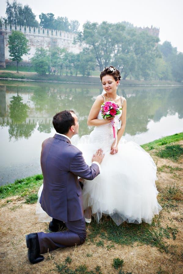 Novio en sus rodillas antes de la novia fotografía de archivo libre de regalías