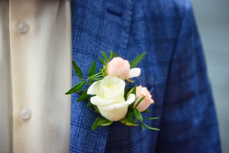 Novio en traje a cuadros azul con un blanco y pálido - boutonniere de la rosa del rosa, imagen de archivo