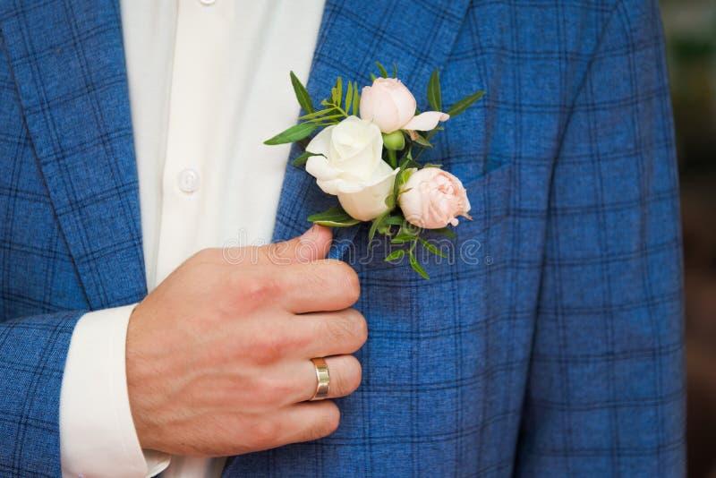 Novio en traje a cuadros azul con un blanco y pálido - rosa BO del rosa imagen de archivo
