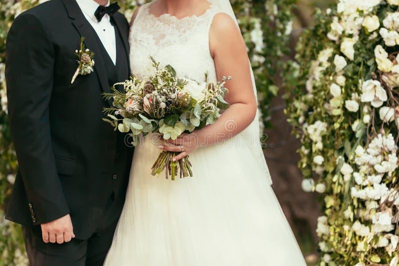 Novio en traje y novia negros en el vestido de boda blanco con rústico fotografía de archivo libre de regalías