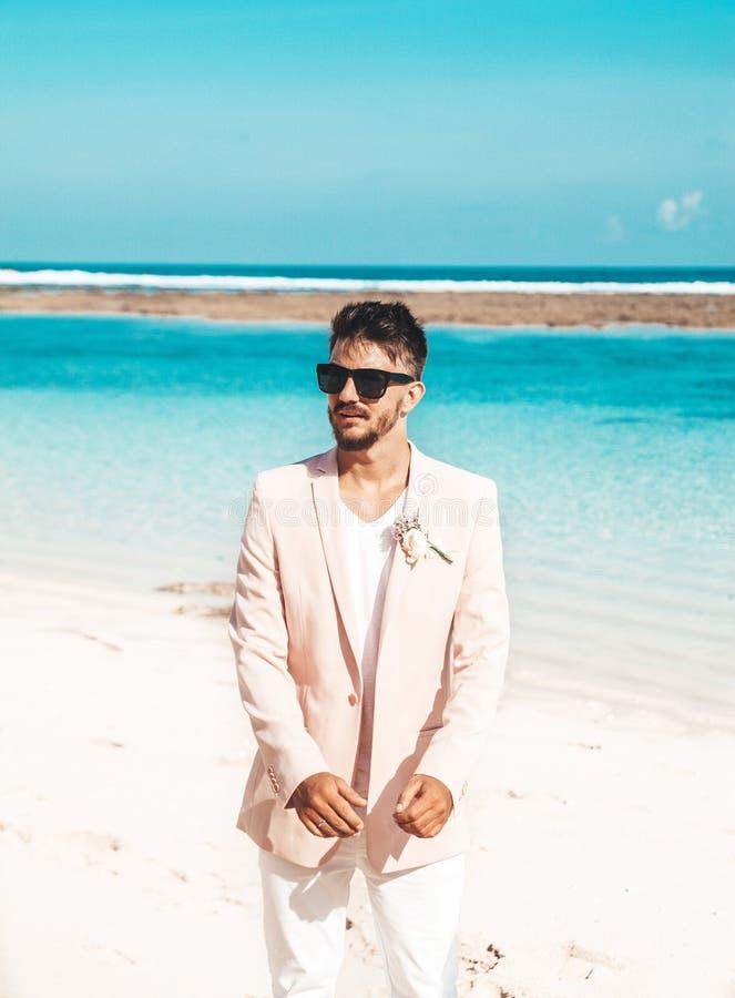 novio hermoso en el traje rosado que presenta en la playa detrás del cielo azul y del océano fotos de archivo