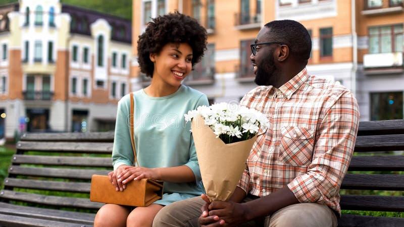 Novio hermoso la primera fecha, hombre de la reunión de la mujer joven que presenta las flores foto de archivo