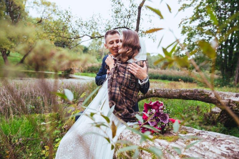Novio que abraza a su novia en parque Pares de la boda imagen de archivo