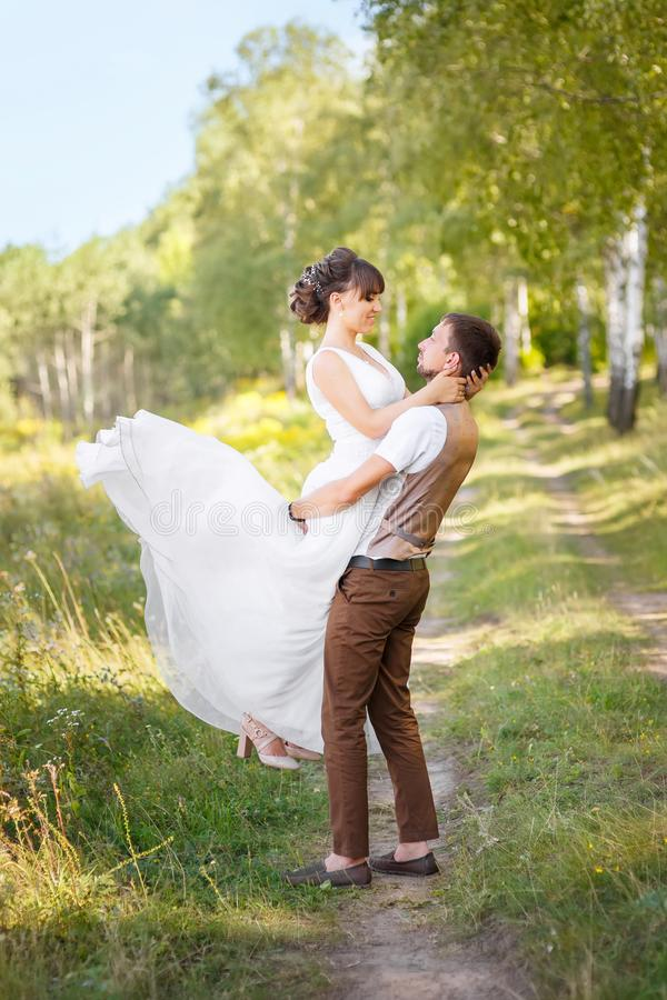 Novio que detiene a la novia en las manos al aire libre imagen de archivo libre de regalías