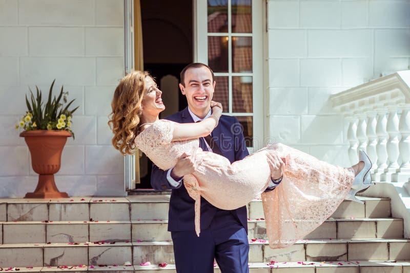 Novio que detiene a la novia en sus brazos imagen de archivo libre de regalías