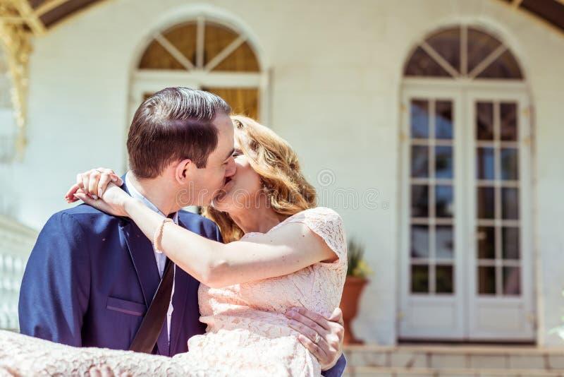 Novio que detiene a la novia en sus brazos imagenes de archivo