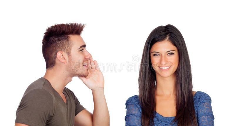 Novio que habla un secreto su novia imagenes de archivo