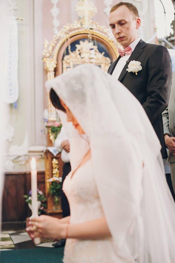 Novio que mira a su novia debajo de velo mientras que ella está rogando con la luz de la vela Pares elegantes felices de la boda  foto de archivo