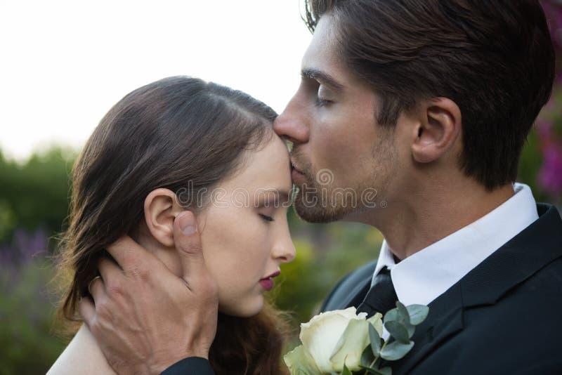 Novio que se besa en la frente de la novia imagenes de archivo