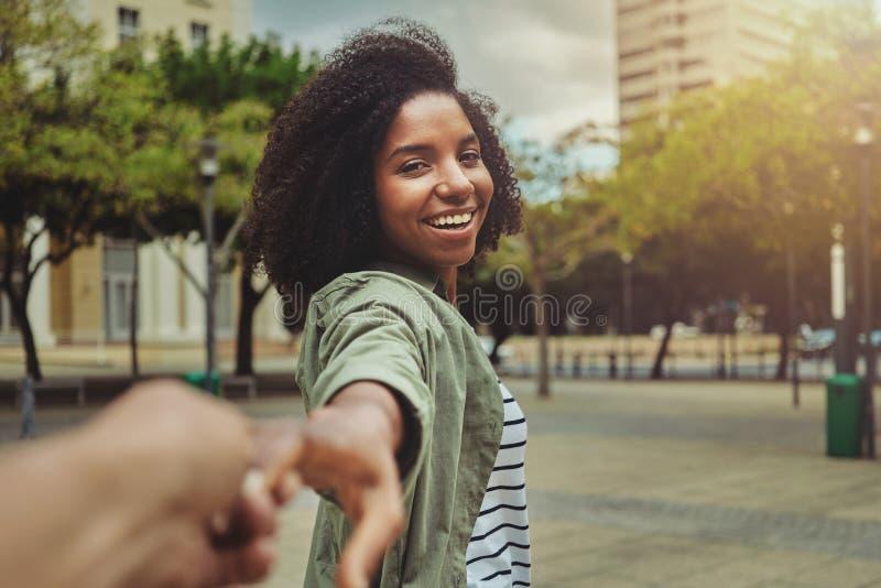Novio que sigue a su novia feliz en la ciudad foto de archivo