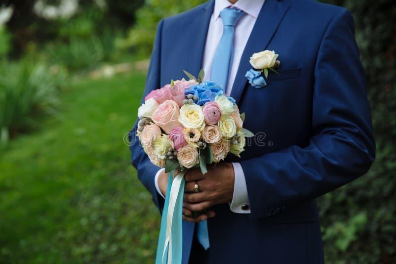 Novio que sostiene el ramo de la boda en su mano imagenes de archivo