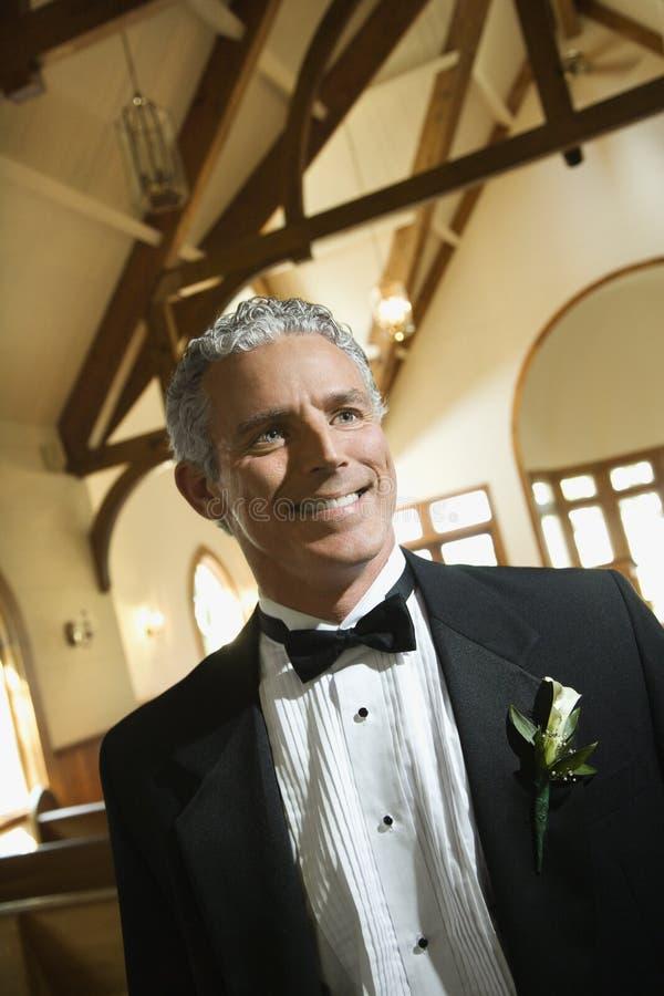 Novio sonriente en iglesia. fotos de archivo
