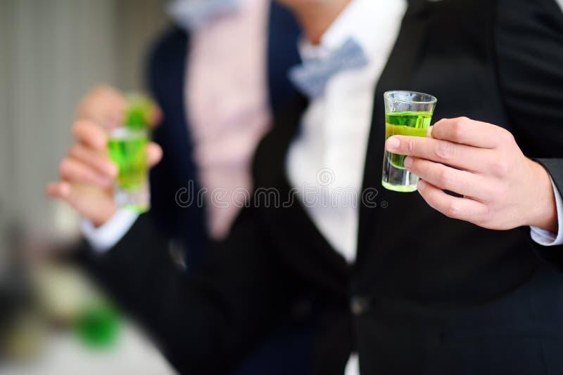 Novio y el mejor hombre que beben el licor fuerte del ajenjo del alcohol durante el banquete de boda imagen de archivo