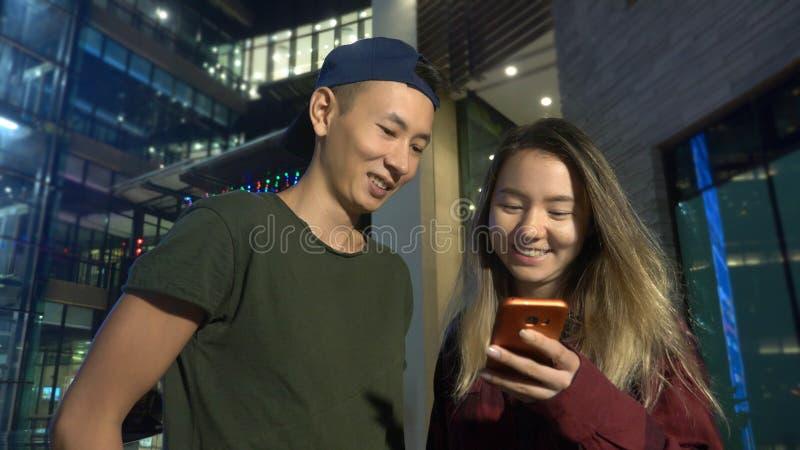 Novio y novia asiáticos jovenes felices de los pares utilice un smartphone mientras que se coloca en una calle de la ciudad en la imagenes de archivo