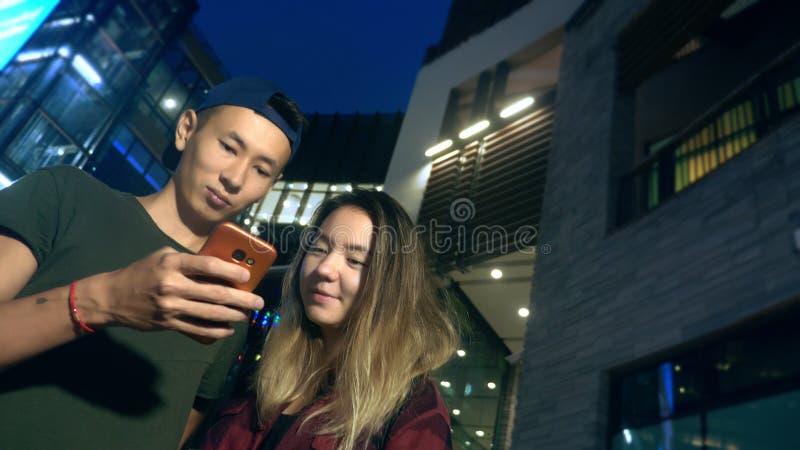 Novio y novia asiáticos jovenes felices de los pares utilice un smartphone mientras que se coloca en una calle de la ciudad en la foto de archivo libre de regalías