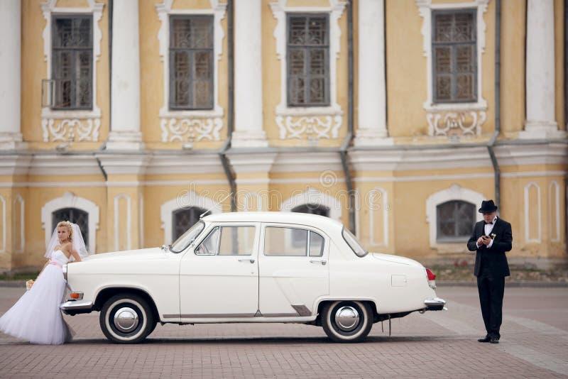 Novio y novia cerca del coche blanco del vintage fotografía de archivo libre de regalías