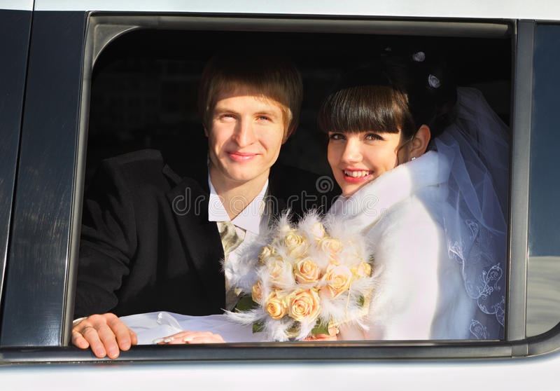 Novio y novia con el ramo que se sienta en limusina imagenes de archivo