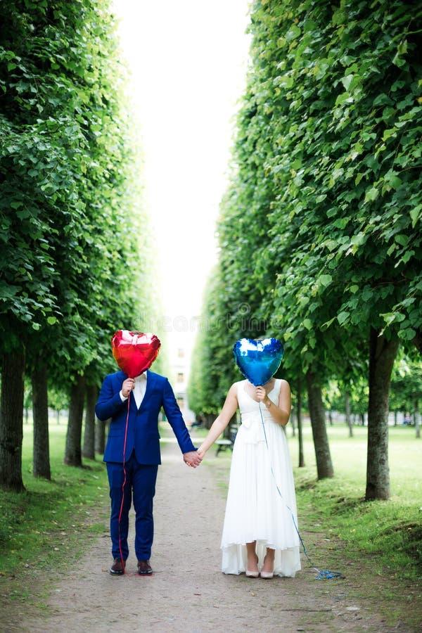 Novio y novia con los globos en la acera fotos de archivo