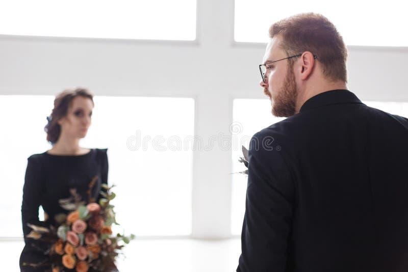 Novio y novia de los pares de la boda que presentan en un estudio blanco Traje y vestido negros Hombre que se coloca de nuevo a c fotos de archivo