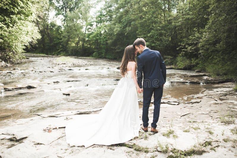 Novio y novia elegantes apacibles elegantes cerca del río con las piedras Pares de la boda en amor imagenes de archivo