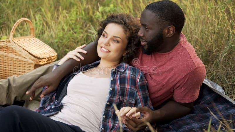 Novio y novia en comida campestre en el parque recreativo, fecha romántica al aire libre imágenes de archivo libres de regalías