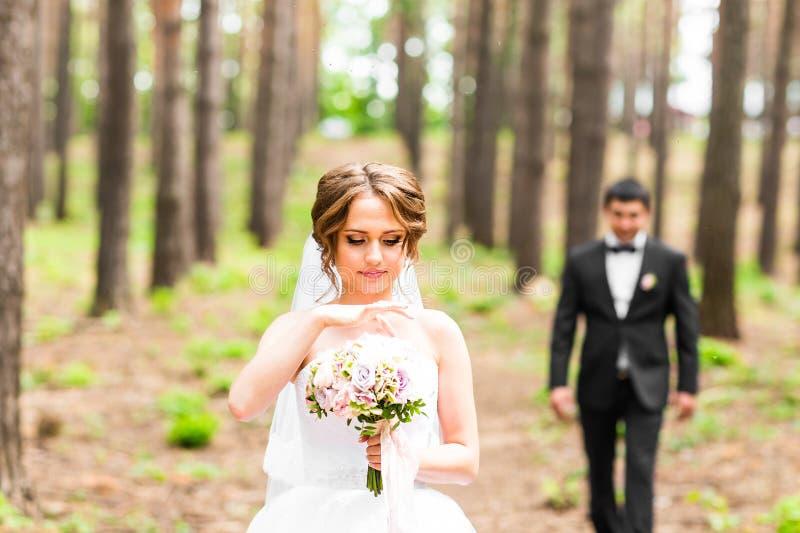 Novio y novia en un parque Ramo nupcial de la boda de flores fotografía de archivo libre de regalías