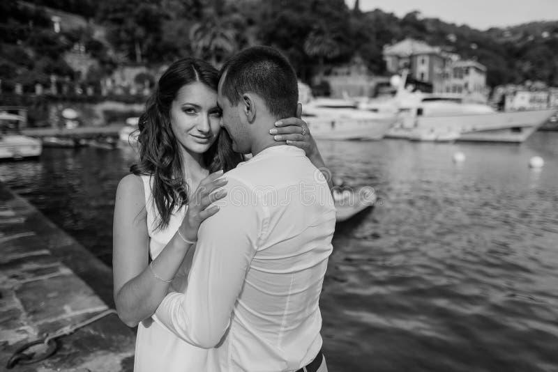 Novio y novia felices en el vestido blanco que abraza el fondo del mar imágenes de archivo libres de regalías