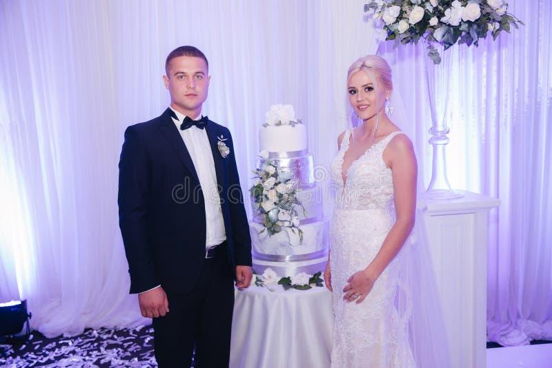 Novio y novia hermosos en soporte del restaurante cerca del pastel de bodas newlyweds foto de archivo libre de regalías