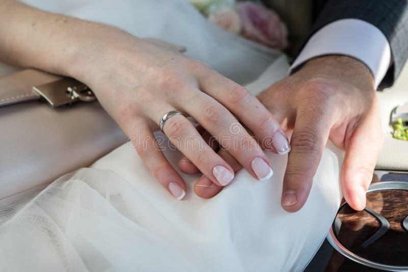 Novio y novia que llevan a cabo las manos con los anillos de bodas imágenes de archivo libres de regalías
