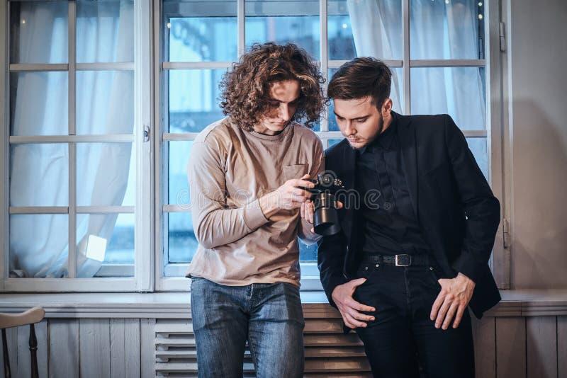 Novisfotograf som bläddrar de resulterande fotona med hans kund i studion royaltyfri bild