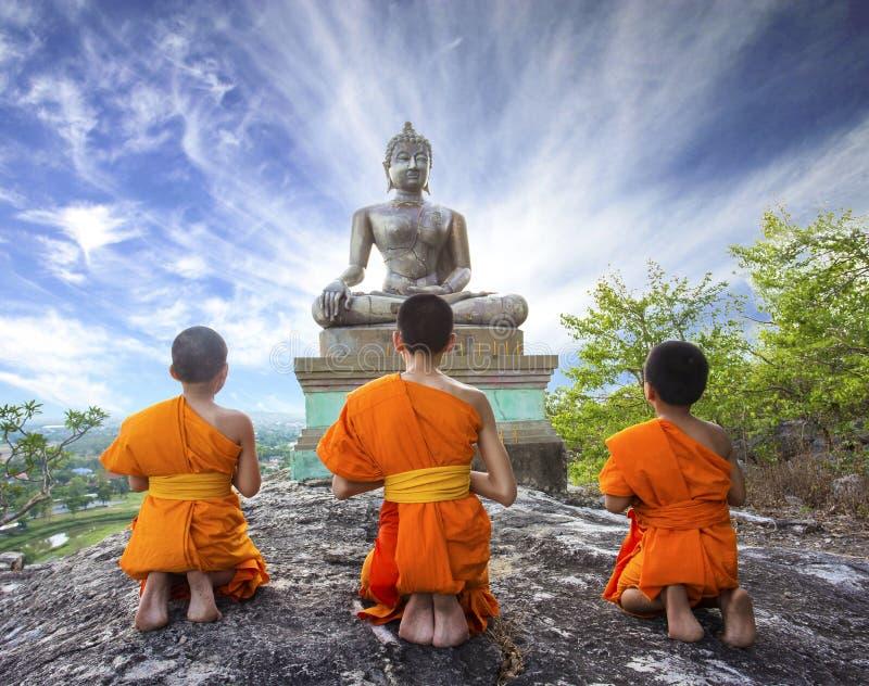 Novismunk som ber till Buddha i den Phrabuddhachay templet royaltyfria foton
