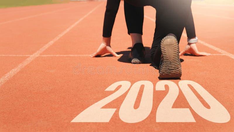 2020 Novo ano, Athlete Woman começando na linha para começar a funcionar com o número 2020 Comece com o novo ano foto de stock royalty free