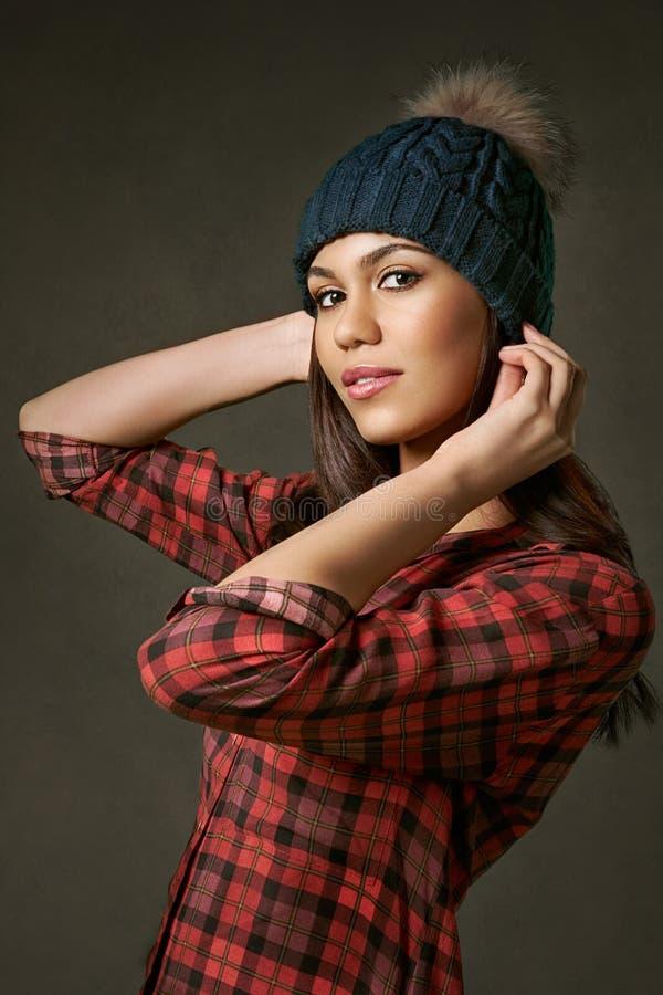 Novo, atrativo, mulher em uma camisa de manta que ajusta um chapéu do inverno imagem de stock royalty free