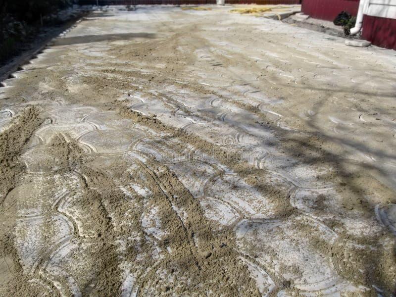 Novo colocou os pavimentos cobertos com a areia Uma das fases de colocar pavimentos está usando a areia seca para encher no meio  imagem de stock royalty free