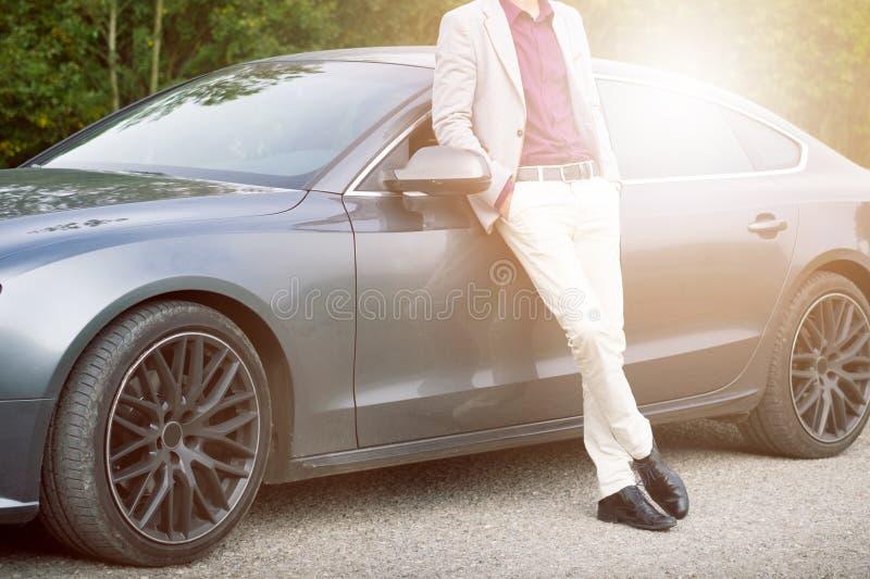 Novo, feliz, homem de negócio no carro Homem nos ternos que estão pelo caro, carro desportivo Homem novo bem sucedido foto de stock