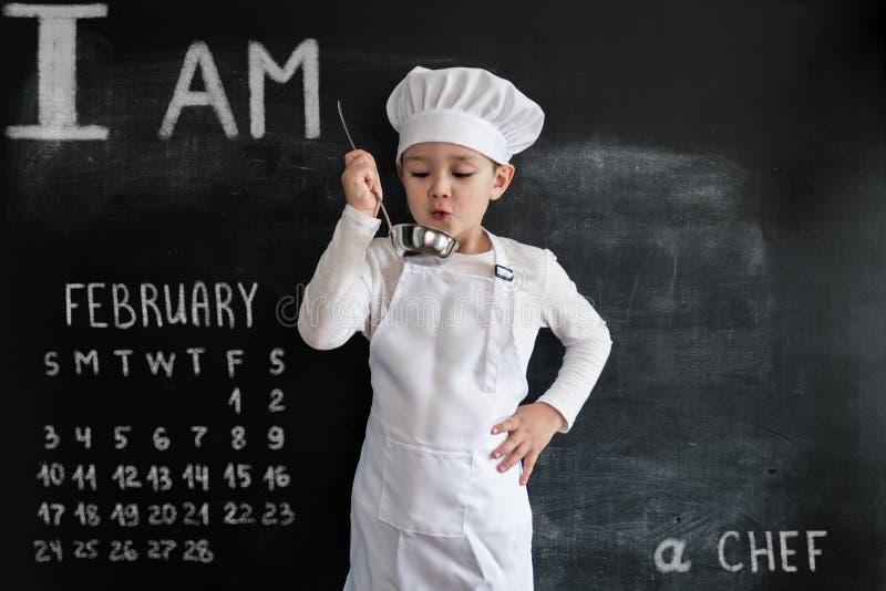 ` Novo s do menino que está o quadro-negro próximo que verifica a sopa Menino novo do cozinheiro chefe Conceito de projeto criati imagem de stock